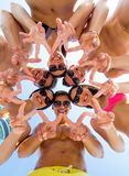 Smiling friends in circle on summer beach. Friendship, happiness, summer vacation, holidays and people concept - group of smiling friends wearing swimwear and Stock Photo