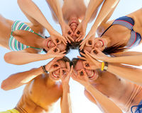 Smiling friends in circle on summer beach. Friendship, happiness, summer vacation, holidays and people concept - group of smiling friends wearing swimwear Royalty Free Stock Image