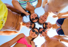Smiling friends in circle on summer beach. Friendship, happiness, summer vacation, holidays and people concept - group of smiling friends wearing swimwear Royalty Free Stock Photography