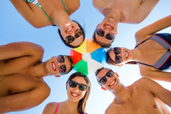 Smiling friends in circle on summer beach. Friendship, happiness, summer vacation, holidays and people concept - group of smiling friends wearing swimwear Royalty Free Stock Photo