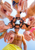 Smiling friends in circle on summer beach. Friendship, summer vacation, gesture and people concept - group of smiling friends wearing swimwear and pointing Stock Image