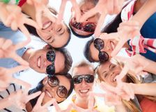 Smiling friends in circle on summer beach. Friendship, summer vacation, holidays and people concept - group of smiling friends showing victory gesture in circle Royalty Free Stock Photos