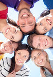 Smiling friends in circle on summer beach. Friendship, summer vacation, holidays and people concept - group of smiling friends standing in circle over blue sky Royalty Free Stock Images