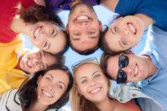 Smiling friends in circle on summer beach. Friendship, summer vacation, holidays and people concept - group of smiling friends standing in circle over blue sky Royalty Free Stock Photography
