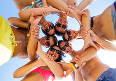 Smiling friends in circle on summer beach. Friendship, summer vacation, teamwork and people concept - group of smiling friends wearing swimwear standing in Stock Photos