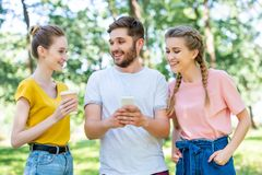 Smiling friends with coffee to go using smartphone together. In park royalty free stock photography