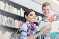 Smiling friends communicating over book against shelf at university library stock image