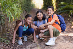 Smiling friends crouching on field at natural parkland. Portrait of smiling friends crouching on field at natural parkland Royalty Free Stock Images