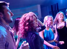 Smiling friends dancing in club. Party, holidays, celebration, nightlife and people concept - smiling friends dancing in club Royalty Free Stock Photos