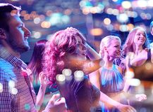 Smiling friends dancing in club. Party, holidays, celebration, nightlife and people concept - smiling friends dancing in club Royalty Free Stock Photo