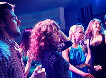 Smiling friends dancing in club. Party, holidays, celebration, nightlife and people concept - smiling friends dancing in club Royalty Free Stock Images