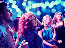 Smiling friends dancing in club. Party, holidays, celebration, nightlife and people concept - smiling friends dancing in club Stock Photography
