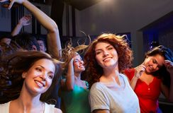Smiling friends dancing in club. Party, holidays, celebration, nightlife and people concept - smiling friends dancing at concert in club Royalty Free Stock Photography
