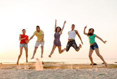 Smiling friends dancing and jumping on beach. Friendship, summer vacation, holidays, party and people concept - group of smiling friends dancing and jumping on stock image