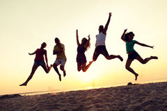 Smiling friends dancing and jumping on beach Royalty Free Stock Images