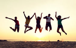 Smiling friends dancing and jumping on beach Royalty Free Stock Photo