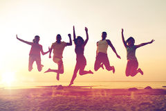Smiling friends dancing and jumping on beach. Friendship, summer vacation, holidays, party and people concept - group of smiling friends dancing and jumping on Royalty Free Stock Photos