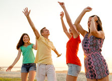 Smiling friends dancing on summer beach Royalty Free Stock Photo