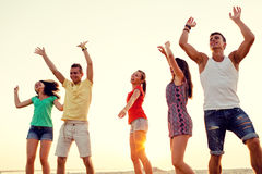 Smiling friends dancing on summer beach Stock Photo