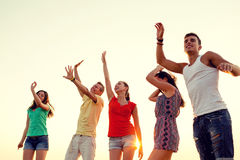 Smiling friends dancing on summer beach. Friendship, summer vacation, holidays, party and people concept - group of smiling friends dancing on beach royalty free stock photo