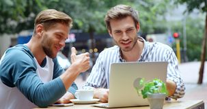 Friends discussing over laptop while having coffee in café 4k. Smiling friends discussing over laptop while having coffee in café 4k stock footage