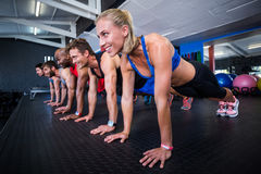 Smiling friends doing push-ups in gym Royalty Free Stock Images