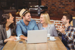 Smiling friends drinking coffee and laughing Royalty Free Stock Photos