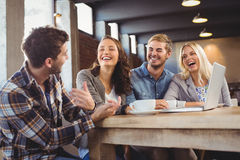 Smiling friends drinking coffee and laughing. At coffee shop Stock Photos