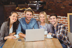Smiling friends drinking coffee and using laptop Royalty Free Stock Images