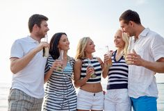 Smiling friends with drinks in bottles on beach Royalty Free Stock Photos