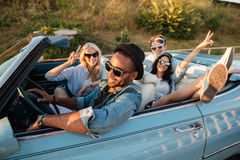 Smiling friends driving car and showing peace sign in summer Stock Photography