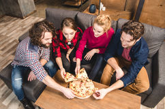 Smiling friends eating pizza Stock Images