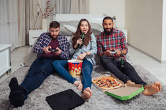 Smiling friends eating pizza and playing computer games at home Royalty Free Stock Images