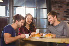 Smiling friends enjoying coffee and croissants together Royalty Free Stock Photography