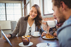 Smiling friends enjoying coffee and looking at tablet Royalty Free Stock Image