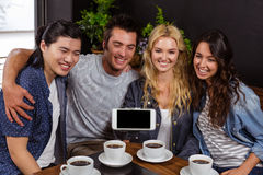 Smiling friends enjoying coffee and taking selfie Stock Photos
