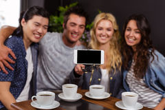 Smiling friends enjoying coffee and taking selfie Stock Image