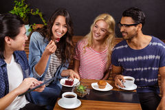 Smiling friends enjoying coffee together and using technologies Royalty Free Stock Photo