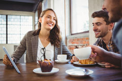 Smiling friends enjoying coffee and using at tablet Stock Image
