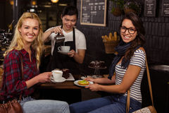Smiling friends enjoying pastries Stock Photography