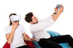 Smiling friends experiencing virtual reality glasses seated on beanbags isolated on white background. Stock Photo