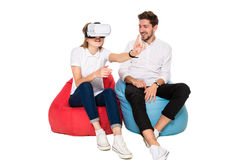 Smiling friends experiencing virtual reality glasses seated on beanbags isolated on white background. Royalty Free Stock Image