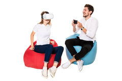 Smiling friends experiencing virtual reality glasses seated on beanbags isolated on white background. Stock Photography