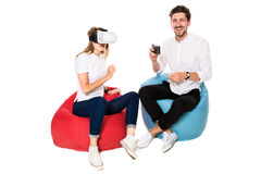 Smiling friends experiencing virtual reality glasses seated on beanbags isolated on white background. Stock Images