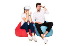 Smiling friends experiencing virtual reality glasses seated on beanbags isolated on white background. Stock Photos