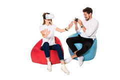 Smiling friends experiencing virtual reality glasses seated on beanbags isolated on white background. Royalty Free Stock Photo