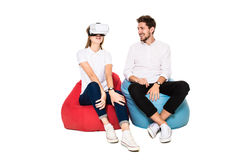 Smiling friends experiencing virtual reality glasses seated on beanbags isolated on white background. Stock Image