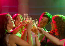 Smiling friends with glasses of champagne in club Royalty Free Stock Image