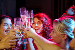 Smiling friends with glasses of champagne in club Royalty Free Stock Photography