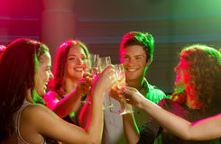 Smiling friends with glasses of champagne in club Stock Photo